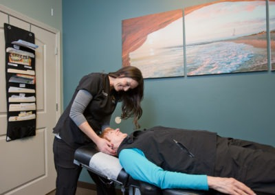 Woman lying face up on table with chiropractor making neck adjustment