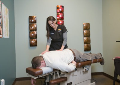 Man lying face down on table with chiropractor checking spine alignment