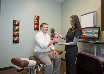Chiropractor administering grip test for male patient
