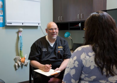 Chiropractor consulting patient on health condition